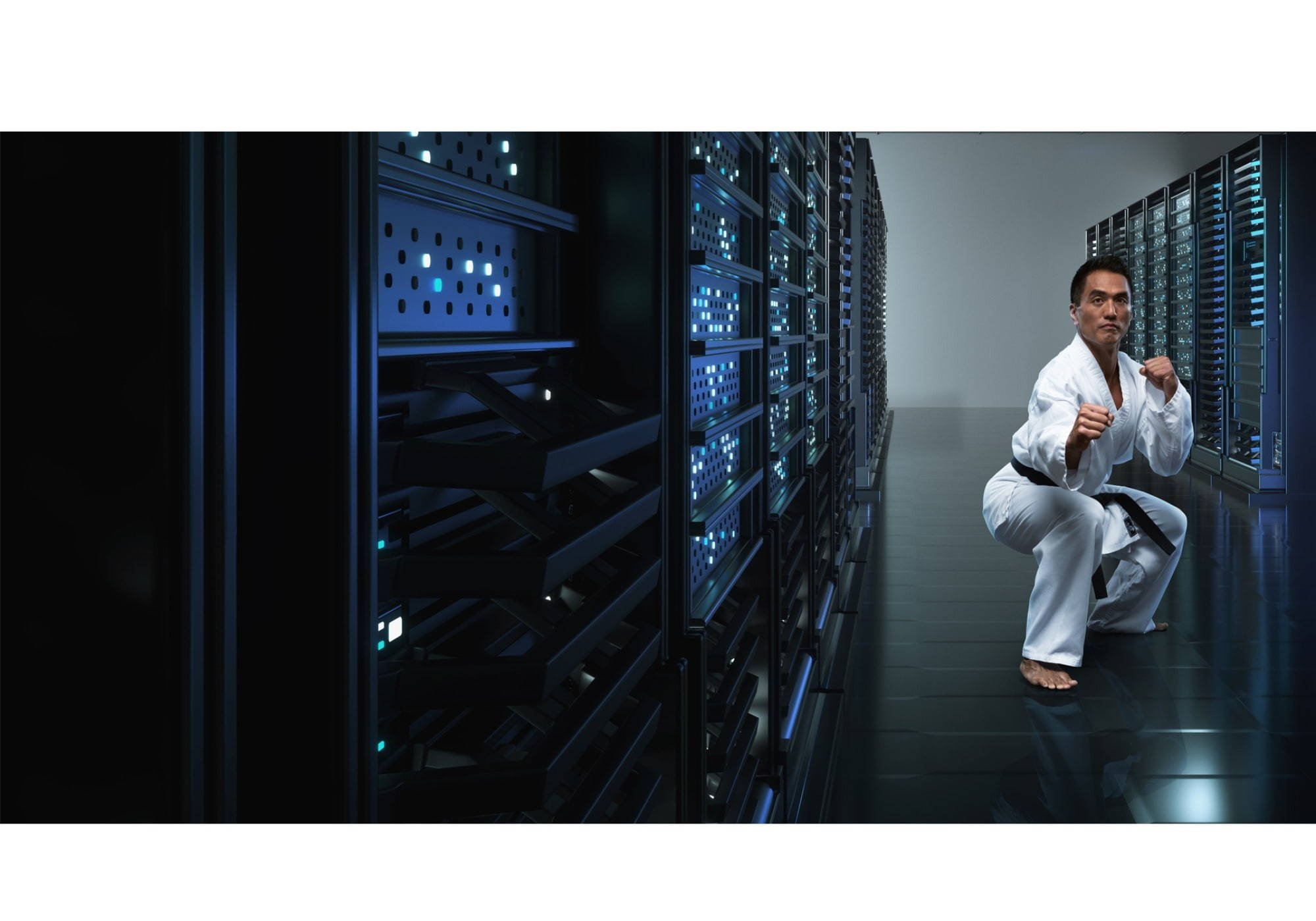 A man in a martial arts stance in a tech server room to indicate protection.