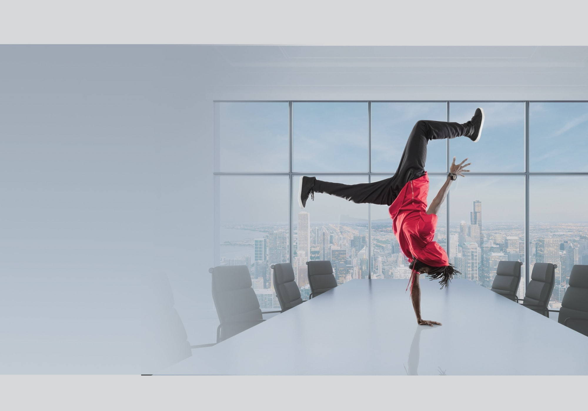 A person breakdancing on a meeting table to demonstrate agility.